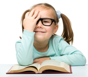 Little girl reads a book while wearing glasses